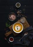Суп тыквы с сливк, семена и специи в деревенском шаре металла над grunge чернят предпосылку Взгляд сверху Стоковые Фото