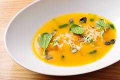 Суп тыквы cream с сыром, зелеными цветами и семенами тыквы, isolat Стоковое Фото