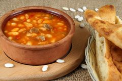 Суп фасоли в посуде страны глины на таблице с lavash Стоковое Фото