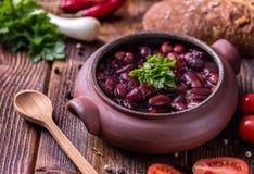 Суп фасоли в домашнем произведенном шаре с томатами на деревянном столе Стоковое Фото