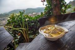 Суп цветка горячего Daylily китайский с семенить свининой на деревянном столе с садом и горным видом Стоковые Фотографии RF