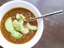 Суп чечевицы с авокадоом в белом шаре с ложкой Стоковые Изображения