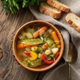 Суп яркого весеннего овоща диетический вегетарианский Взгляд сверху, предпосылка коричневого цвета деревенская деревянная, linen  Стоковые Изображения RF