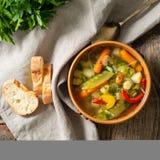 Суп яркого весеннего овоща диетический вегетарианский Взгляд сверху, предпосылка коричневого цвета деревенская деревянная, linen  Стоковые Фото