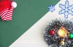 Сусаль ` s Нового Года, шарики, горящая свеча, красная крышка, снежинки на зеленой предпосылке Место для надписи Стоковая Фотография
