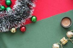Сусаль ` s Нового Года, шарики и свеча на зеленой и красной предпосылке Место для надписи Стоковая Фотография