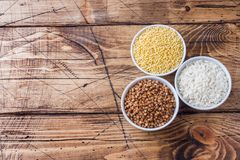 Сухая бакалея гроутов Рис, гречиха и пшено на деревянной предпосылке стоковые фото