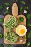 Сухие гнезда макарон с шпинатом Зеленый цвет макаронных изделий на темной предпосылке с шпинатом выходит стоковые изображения