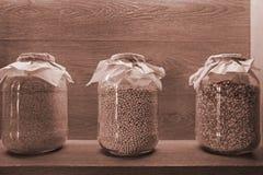 Сухие зерна в ясных стеклянных опарниках на полке с освещением стоковые фото
