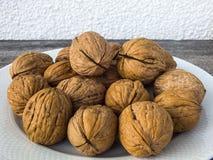 Сухие картины грецкого ореха в различных концепциях, грецких орехах в плитах и сумках готовых для того чтобы представить, картины Стоковое Изображение RF