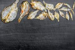 Сухие рыбы и солнечный на черном деревянном поле Стоковое Изображение
