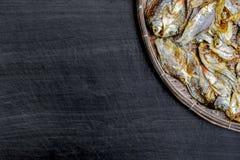 Сухие рыбы от солнца на черном деревянном поле Стоковая Фотография