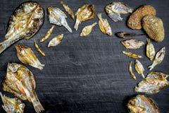 Сухие рыбы с солнечным на черном деревянном поле Стоковое Изображение RF