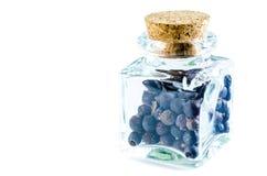 Сухие ягоды можжевельника в стеклянной бутылке изолированной на белизне стоковое фото