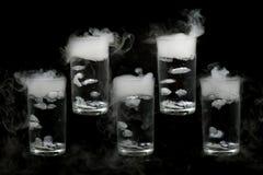 Сухой лед 5 в стекле воды изолированном на черной предпосылке дым, конец вверх стоковое фото rf