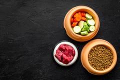 Сухой органический корм для домашних животных с свежими овощами и мясо в пластичном шаре для подавая собак на черном взгляд сверх Стоковые Изображения