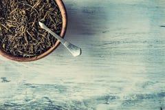 Сухой чай в деревянной плите на деревянном столе Стоковые Фотографии RF