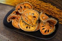 Сухой чай плодоовощ Bael (marmelos Aegle) на темной винтажной древесине Стоковое Изображение RF