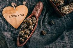 Сухой черный чай Свернутые листья в большом жемчуге Копните форменное керамическое сердце с словами я тебя люблю Китайский чай от Стоковые Фотографии RF