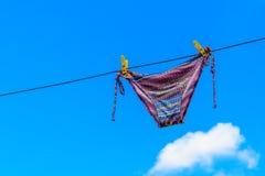 Сушить женский купальник вися на веревочке против голубого неба стоковые фото