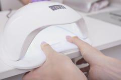 Сушить ногти в лампе ультрафиолетова Маникюр салона конец вверх стоковые изображения