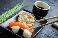 Суши в черное керамическом съеденные с палочками Стоковые Фото