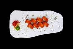 Суши Калифорнии Maki - крен сделанный из мяса краба, авокадоа, огурца внутрь Взгляд сверху Изолировано на черной предпосылке Стоковые Изображения