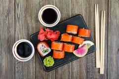 Суши крена Филадельфии с семгами, креветкой, авокадоом, плавленый сыр служили на деревянной предпосылке Меню суш Стоковое фото RF