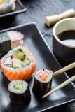 Суши на черное керамическом съеденные с палочками Стоковые Изображения RF