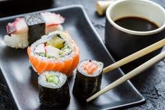Суши на черное керамическом съеденные с палочками Стоковое Изображение RF