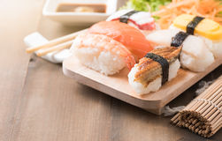 Суши с соусом и wasabi на старой коричневой деревянной плите стоковое фото rf