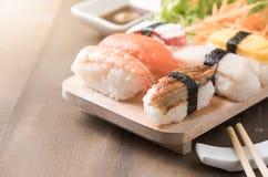 Суши с соусом и wasabi на старой коричневой деревянной плите стоковые фото