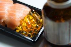 Суши служили с кучами капсул рыбьего жира с коричневой бутылкой i Стоковые Изображения