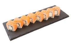 Суши Maki - крен Филадельфии сделанный из плавленого сыра внутрь на черной поверхности сланца шифера или камня на белой предпосыл Стоковое Изображение RF