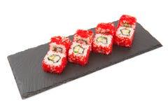 Суши Maki - крен Филадельфии сделанный из плавленого сыра внутрь на черной поверхности сланца шифера или камня на белой предпосыл Стоковое Фото