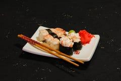 Суши Nigiri установили на белую плиту на черной предпосылке Японская еда Азиатский вкусный обедающий Стоковое Изображение
