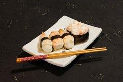 Суши Nigiri установили на белую плиту на черной предпосылке Японская еда Азиатский вкусный обедающий Стоковые Изображения RF