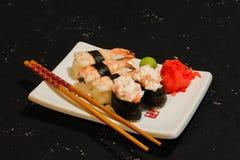 Суши Nigiri установили на белую плиту на черной предпосылке Японская еда Азиатский вкусный обедающий Стоковое Изображение RF