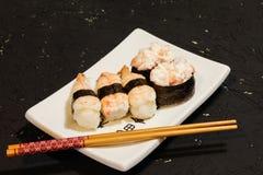 Суши Nigiri установили на белую плиту на черной предпосылке Японская еда Азиатский вкусный обедающий Стоковая Фотография RF