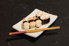 Суши Nigiri установили на белую плиту на черной предпосылке Японская еда Азиатский вкусный обедающий Стоковые Фотографии RF