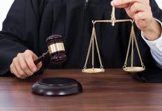 Судите держать масштаб веса пока поражающ молоток на столе Стоковое фото RF