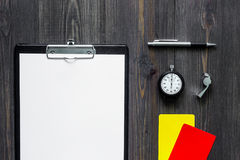 Судить спорт Желтые и красные карточки рефери, свисток и секундомер на деревянном модель-макете взгляд сверху предпосылки Стоковая Фотография
