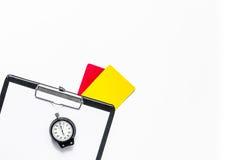 Судить футбола Желтые и красные карточки рефери, секундомер, пусковая площадка, на белом copyspace взгляд сверху предпосылки Стоковая Фотография