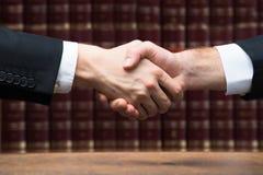 Судья и клиент тряся руки против книг Стоковые Фотографии RF