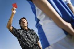 Судья-рефери показывая красную карточку к игроку Стоковые Изображения