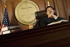 Судья сидя в зале судебных заседаний стоковое изображение