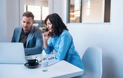 2 сфокусировали предпринимателей работая на компьтер-книжке в офисе Стоковые Фотографии RF