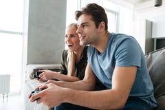 Сфокусированная дама и человек играя видеоигры дома в живущей комнате Стоковые Фотографии RF