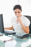 Сфокусированная коммерсантка выпивая стекло воды на ее столе Стоковое Фото