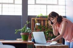 Сфокусированная коммерсантка говоря на ее мобильном телефоне и используя компьтер-книжку Стоковые Фото